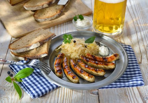 Nürnberger Rostbratwürste mit Kraut und Meerrettich traditionell auf dem Zinnteller mit Brot serviert - Fried Bavarian sausages from Nuremberg with sauerkraut and horseradish served on a pewter plate